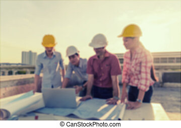 Blurred engineers group meeting on top of terrace in construction site.vintage tone.