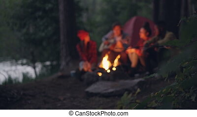 Blurred footage of travelers romantic young people sitting near campfire in forest, playing the guitar and singing. Focus on tree branch with leaves in foreground.