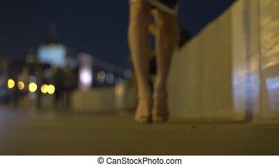 Blurred girl in high heels walking at the camera at night. Shallow focus 4K shot