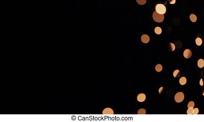Blurred globular highlights of gold on black background