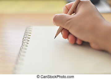 Blurred hand writing on notebook.