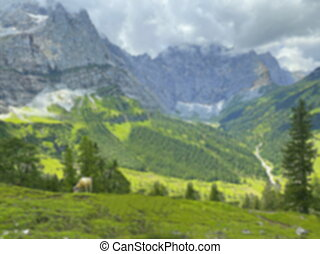 Blurred idyllic landscape in the Alps with brown cows graze at fresh green meadows, snowcapped mountain tops in the background. Nationalpark Grosser Ahornboden Eng-Alm. Tyrol, Austria