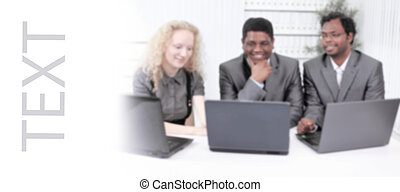 blurred image, employees look at the laptop monitor, sitting at the table