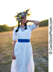 Blurred image of a young woman in a long white embroidered shirt and in a wreath of wild flowers in the field at sunset.