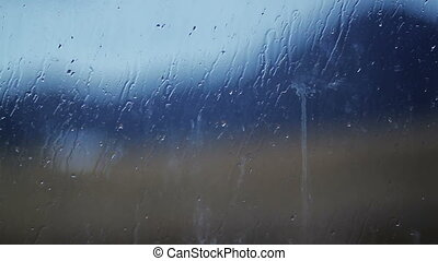 Blurred image of mountainson the background a rain spattered window glass