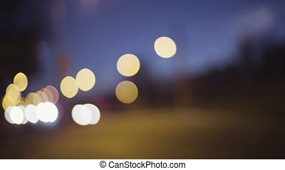Blurred image of night city traffic, cars move along the road.