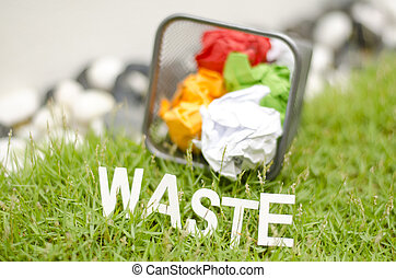blurred image of word waste made from wood in arc position placed on green grass and centered. used colour paper in thrash can and blur background;