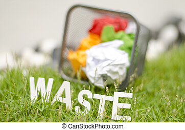blurred image of word waste made from wood in arc position placed on green grass. ball used colour paper in thrash can and blur background