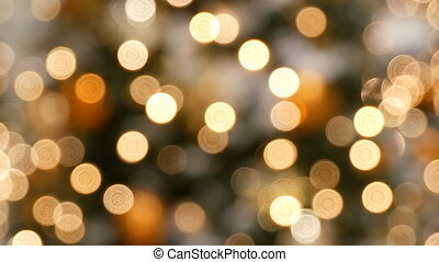 Blurred lights of Christmas garlands in golden silver and...