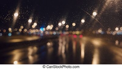 Blurred lights of night freeway through windshield with working wiper