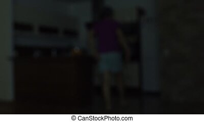 Blurred man opening refrigerator at night. Gluttony or...