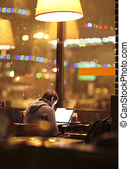 Blurred man with laptop at cafe background