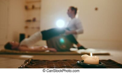 Blurred - massage session in candles - traditional thailand stretching for young female model