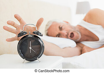 Blurred mature man extending hand to alarm clock
