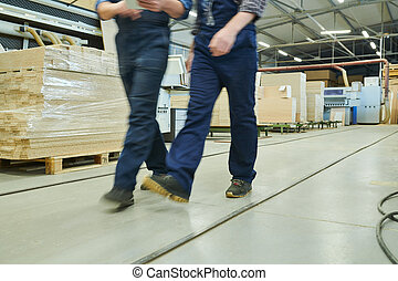 Blurred motion of factory men in overalls