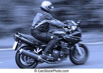 blurred motorcyclist in blue