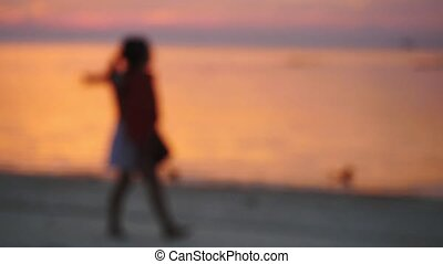 Blurred mum with Little girl walk on the beach during...