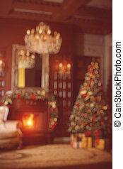 Blurred New Year's luxurious interior with Christmas tree spruce, fire in the fireplace and gifts.