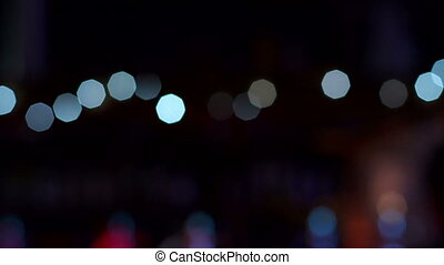 Blinking blurred lights in the dark in a restaurant or cafe. Slow motion.