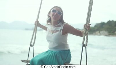 Blurred of pretty young happy woman relaxes on the swing at the stones beach in slow motion