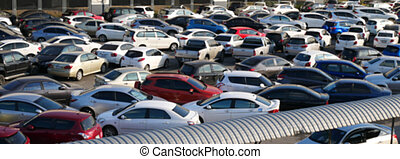 blurred outdoor parking lot full of cars