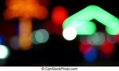 Blurred outdoor restaurant glowing lights at night with colorful bokeh light effect.