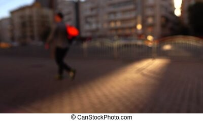 Blurred people and cars on evening street. 4K background bokeh clip