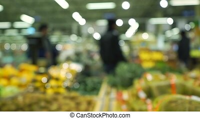 Blurred people buying fruits in a supermarket. Slow motion video