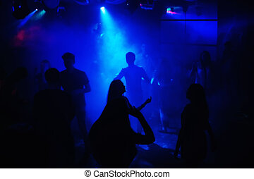 blurred people dancing on dance floor at event in a night club