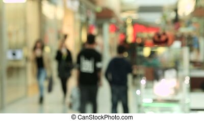Blurred people in motion, people walking in shopping center, out of focus movie shot