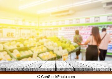blurred people shopping with wooden tabletop