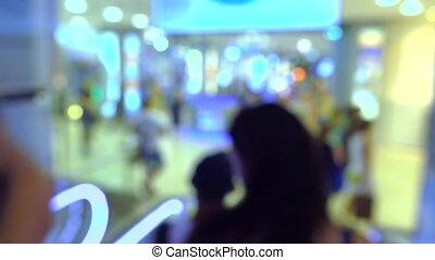 Blurred people using escalator in modern shopping mall. 4K bokeh video