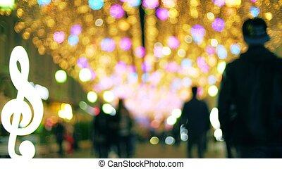 Blurred people walk along illuminated pedestrian area in the...
