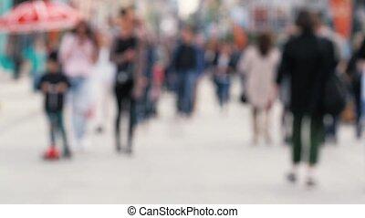 Blurred people walking on street in weekend - People walking...