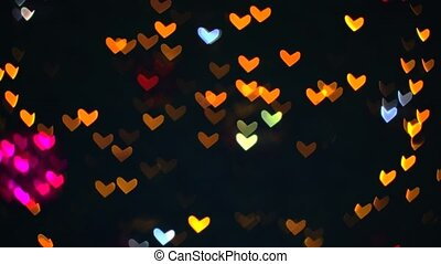 Blurred red orange warm shape hearts blink on tree beautiful  night light in the garden