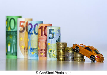 Blurred row of rolled hundred, fifty, twenty, ten and five new euro banknotes and pile of coins with yellow toy expensive sport car. Symbol of financial prosperity, vehicle sale and purchase.