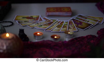 Blurred Scene of fortune-teller forecasting fate with tarot cards. Woman placing cards in order as mystic rite. Halloween divination in spooky esoteric atmosphere.