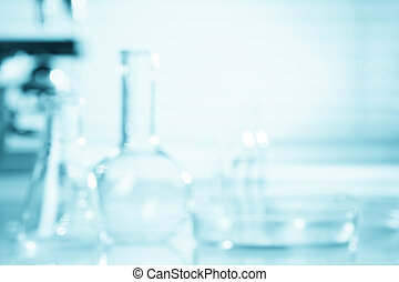 Blurred science background, test tubes and microscope with...