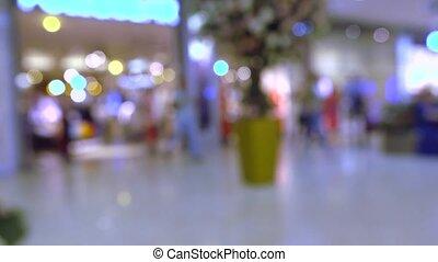 Blurred shop entrance in modern shopping mall. 4K bokeh video