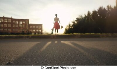Blurred Shopaholic woman in beautiful dress holding many shopping bags walking on the street through the sun during sunset in slow motion.