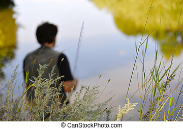 Blurred silhouette of fisherman on the river on a clear summer d