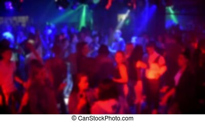 blurred silhouettes of a crowd of dancing people in a nightclub