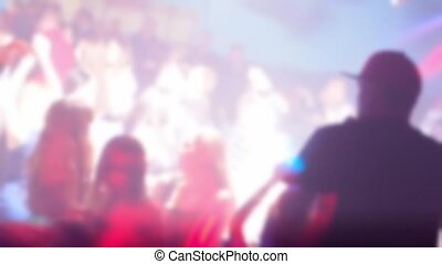 blurred silhouettes of a crowd of dancing people on the dance floor in a nightclub at a party under colorful spotlights. Slow motion out of focus