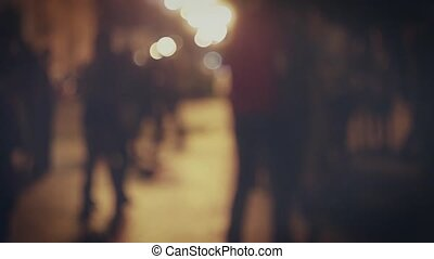 Blurred silhouettes of dancing couples in the night street