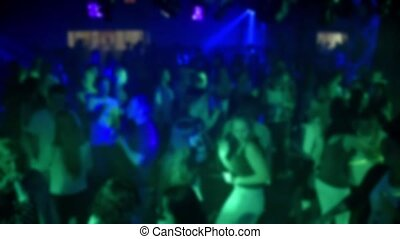 blurred silhouettes of dancing people on the dance floor in a nightclub