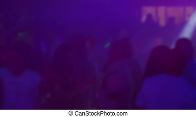 blurred silhouettes of people dancing in a nightclub on the dance floor at a music concert to electronic music with slow motion
