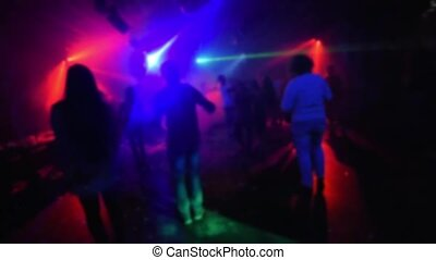 blurred silhouettes of people dancing in a nightclub on the...