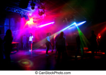 blurred silhouettes of people dancing in a nightclub