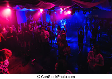 blurred silhouettes of people dancing on dance floor of a night club at concert
