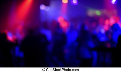 blurred silhouettes of people dancing on the dance floor in a nightclub